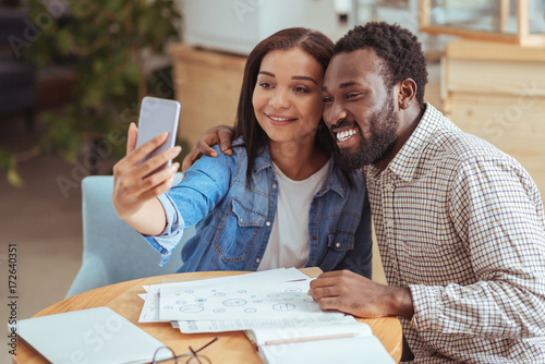 Photo  Cheerful colleagues taking selfie together in coffee shop