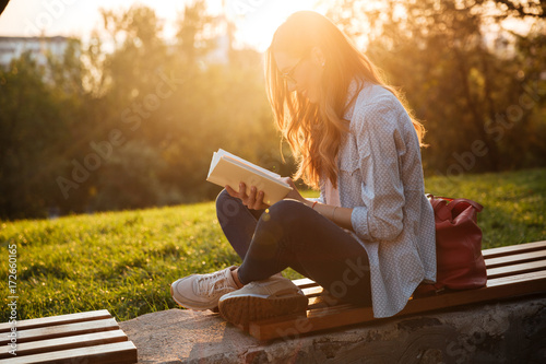 Photo  Side view of smiling woman in eyeglasses sitting on bench