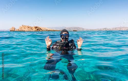 Weibliche Taucherin gibt das OK Zeichen an der Wasseroberfläche