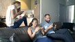 Family playing game on smartphones sitting on sofa at home