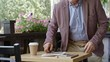 Senior businessman walking and sitting at table in outdoor restaurant, putting on eyeglasses and turning on digital tablet