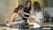 Mother with her daughters using tablet and smartphone in kitchen at home