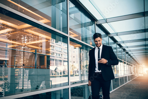 Young businessman walking with mobile phone at airport