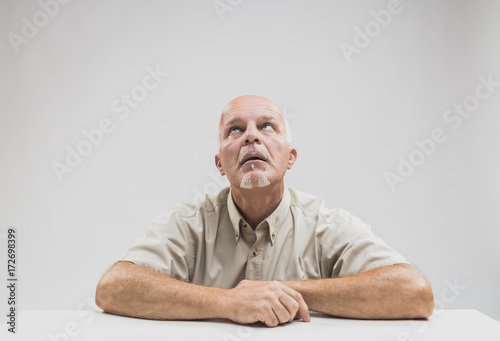 Fotografering  Bored man sitting at table