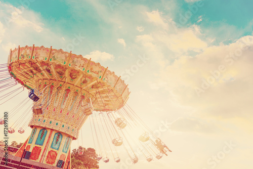 Fotografie, Obraz  carousel ride spins fast in the air at sunset - vintage filter effects - a swing