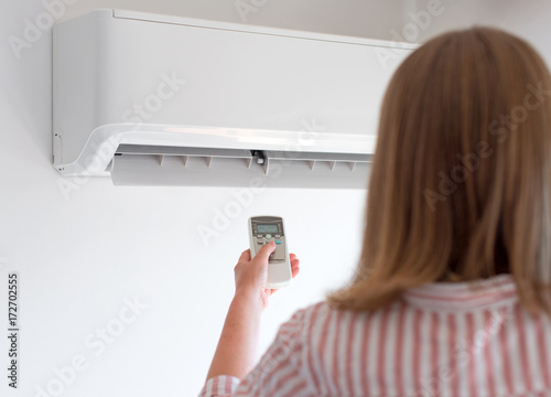 Photo Woman holding remote control aimed at the air conditioner.