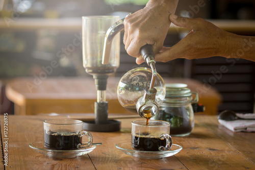 Photo  close up of siphon vacuum, coffee cup and siphon vacuum coffee maker at shop