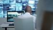 Security team watching CCTV screens in control room, officer talking on radio