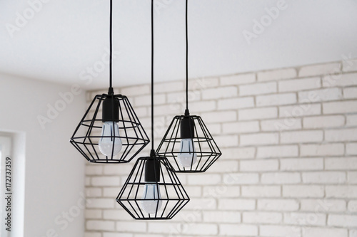 A modern loft chandelier made of black wire in a stylish white interior