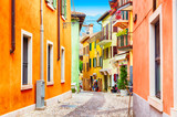 Fototapeta Uliczki - Small town narrow street view with colorful houses in Malcesine, Italy during sunny day. Beautiful lake Garda.