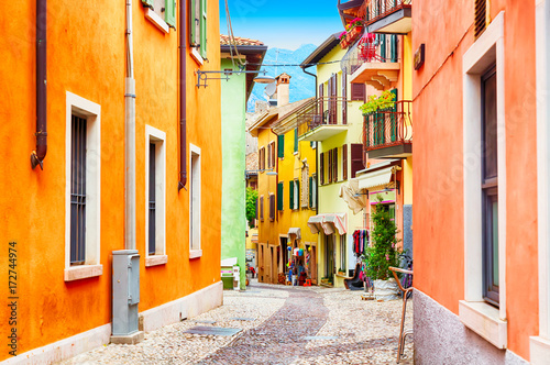 Garden Poster Narrow alley Small town narrow street view with colorful houses in Malcesine, Italy during sunny day. Beautiful lake Garda.