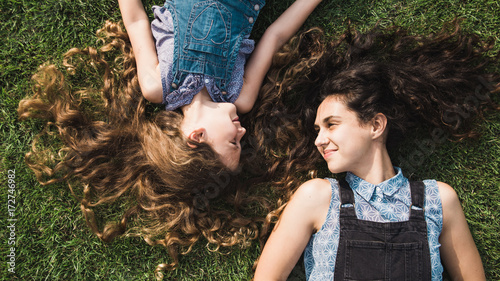 Mother and daughter laying on the green grass looking at each other