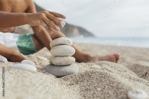 Hand making stone balance on the beach.