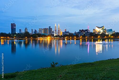 Photo Stands Blue hour view of Kuala Lumpur skyline, capital city of Malaysia as seen from Taman Tasik Titiwangsa.
