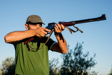Hunter With A Rifle In The Cou...
