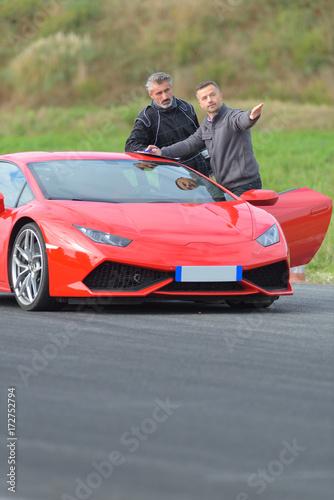 Photo  2 men standing nect to lamborghini race car on track