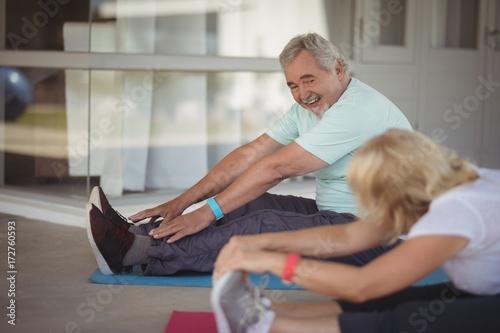 Fotografia  Senior couple performing stretching exercise