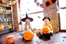 What`s Inside? Two Blonde Curious Siblings Made A Jackolantern, Fairy Is Peeking Inside It, Junior Boy Is Confused, They Are Sitting Down, Near The Window In Decorated Loft Style Of Room