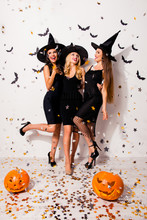 Full Size Of Crazy Glamour Party, Three Mistress In Elegant Wear, With Bright Red Lips, Long Wizard Headwears, Standing Posing On White Wall Background, With Pumpkin Cutted Head, Enjoying, Like Stars!