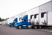 Blue Semi Trucks And Semi Trailers Stand In Row Hardly Near The Warehouse Gate Under Loading And Unloading Process