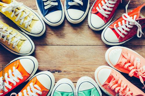Fotografia  Multi Color sneakers on wood background