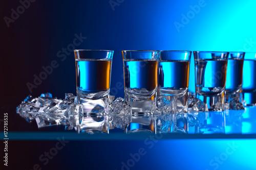 kieliszki-z-nalana-wodka-i-lodem-na-stole-podswietlonym-niebieskim-swiatlem