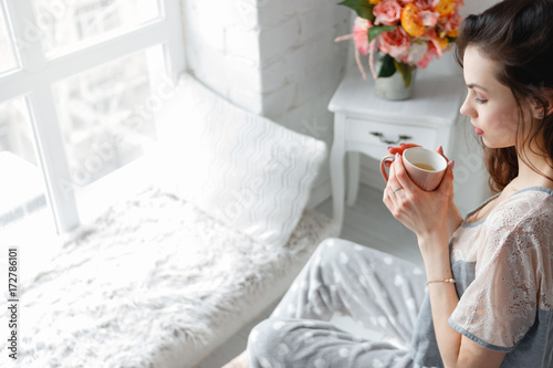 Fototapeta Sensual young woman with cup of tea at home. Every morning ritual for good start of the day. Thoughtfulness and calmness, relaxation and perception concept obraz