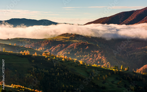 Foto op Canvas Zwart cloud rising above the rolling hills, gorgeous autumnal scenery in mountains at sunrise