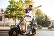 Full length picture of happy african couple rides on motorbike