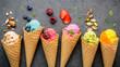 Leinwandbild Motiv Various of ice cream flavor in cones blueberry ,strawberry ,pistachio ,almond ,orange and cherry setup on dark stone background . Summer and Sweet menu concept.