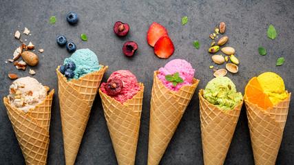 Fototapeta Various of ice cream flavor in cones blueberry ,strawberry ,pistachio ,almond ,orange and cherry setup on dark stone background . Summer and Sweet menu concept.