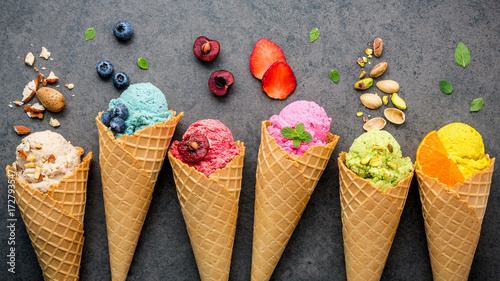In de dag Dessert Various of ice cream flavor in cones blueberry ,strawberry ,pistachio ,almond ,orange and cherry setup on dark stone background . Summer and Sweet menu concept.