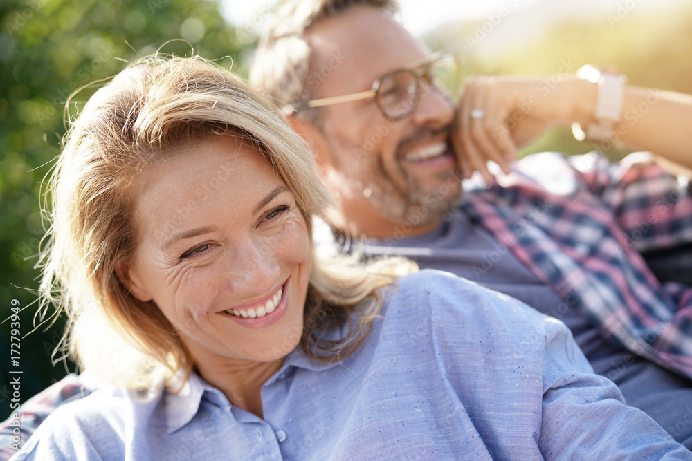 Fototapeta Portrait of mature couple relaxing in outdoor sofa