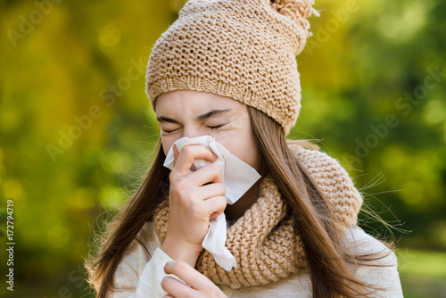 Valokuva  Young woman sneezes in a handkerchief on the street in autumn