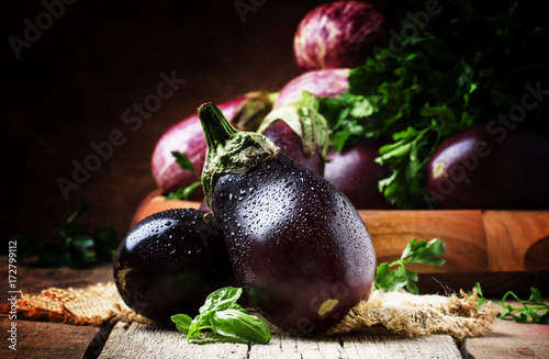 Fresh aubergines on vintage wooden background, selective focus Canvas Print