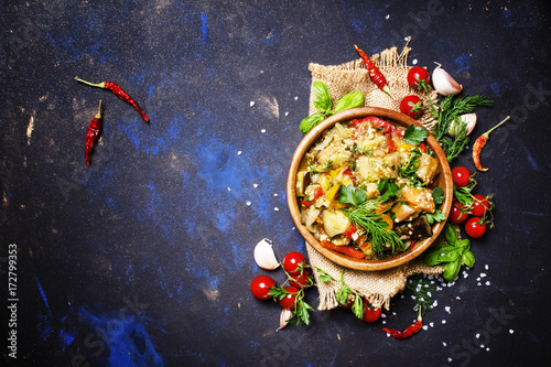 Poster Aromatische Eggplants stewed with pepper, tomato and onion in wooden bowl, top view
