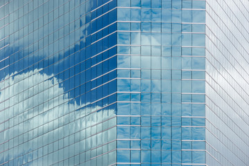 Blue sky and clouds reflecting in windows of modern office building