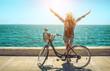 Leinwandbild Motiv Blonde woman in summer hat with her bicycle walking coastline by