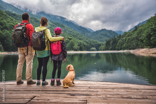 Stickers pour porte Kaki Family with dog standing on a pier