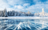 Fototapeta Do pokoju - Blue ice and cracks on the surface of the ice. Frozen lake under a blue sky in the winter. The hills of pines. Winter. Carpathian, Ukraine, Europe.