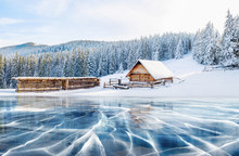 Blue Ice And Cracks On The Surface Of The Ice. Frozen Lake Under A Blue Sky In The Winter. Cabin In The Mountains. Mysterious Fog. Carpathians. Ukraine, Europe