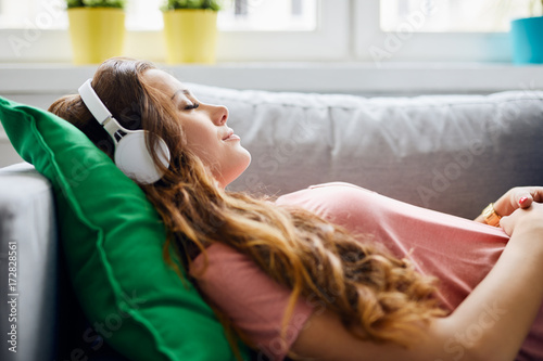 Fotografía  Portrait of a beautiful young woman lying on sofa with headphones on and closed
