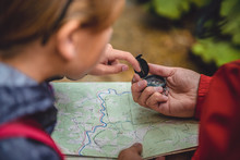 Father And Daughter Hiking In Forest And Checking Map