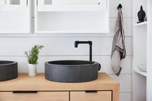 Stone Vessel Sink On Oak Vanity In Rustic Farmhouse Bathroom