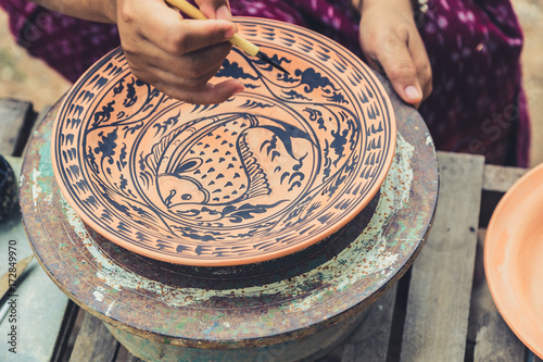Fotografie, Obraz  Artist paint drawing fish in Sukhothai traditional style pattern with black color in earthenware, making of handcraft pottery in Sukhothai, Thailand