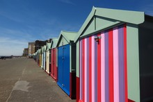 Colorful Painted Beach Huts In A Row On Brighton And Hove Boardwalk In England, UK