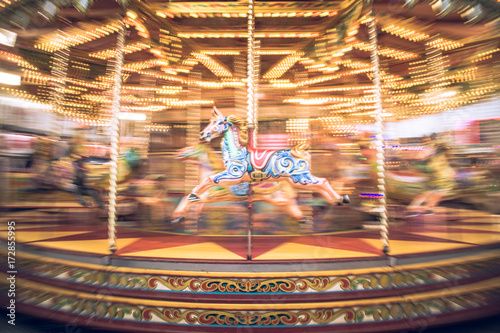 Fotografie, Obraz Motion blurr of vintage carousel horse of amusement ride on merry-go-round carousel