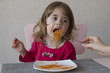Portrait of adorable little girl eating spaghetti sitting at the table