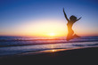 Silhouettes. Girl is jumping beach with beautiful sunset in background
