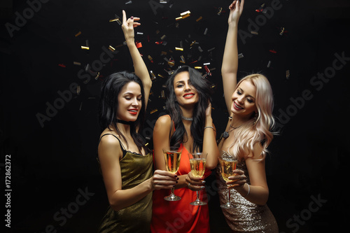 Obraz Young attractive women celebrating a party, drinking champagne and dancing - fototapety do salonu